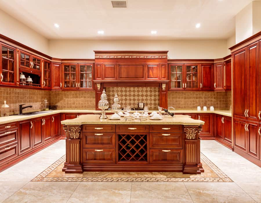 backlit kitchen with red wood cabinets